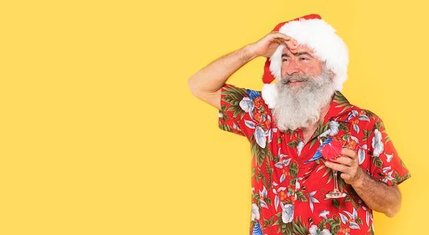 Homem com camisa tropical e chapéu de natal com espaço de cópia