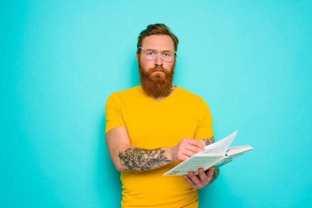 Homem com camiseta amarela está concentrado na leitura de um livro