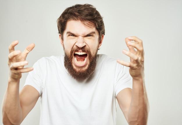 Homem com camiseta branca gesticulando raiva close-up