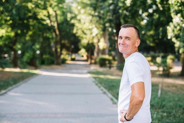 Homem com camiseta branca, olhando para a câmera