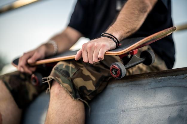 Homem com camiseta preta e shorts segurando um skate preto sobre os joelhos