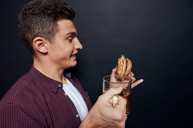 Homem com caneca de cerveja e hambúrguer nas mãos divertido espaço isolado escuro do estúdio de estilo de vida.