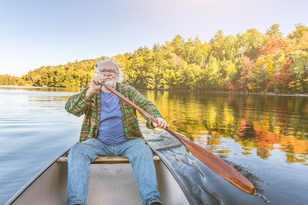 Homem com canoa no lago em um dia ensolarado de outono