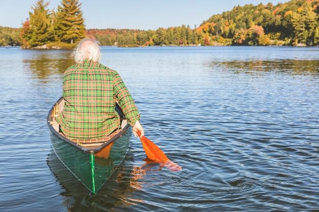 Homem, com, canoa, remando, ligado, um, dia ensolarado, vista traseira