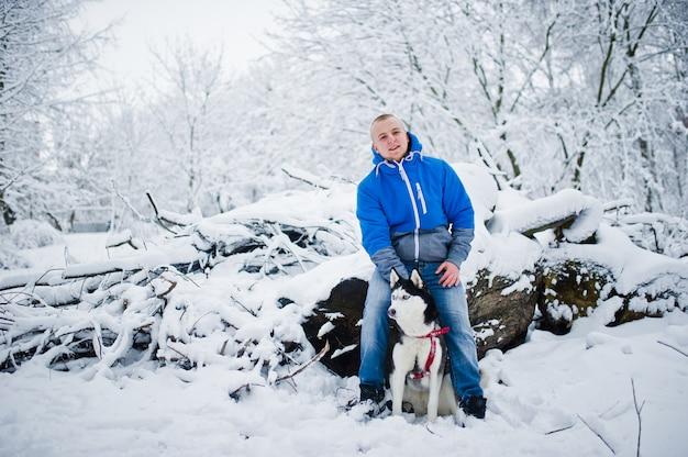 Homem com cão husky no parque de inverno nevado.