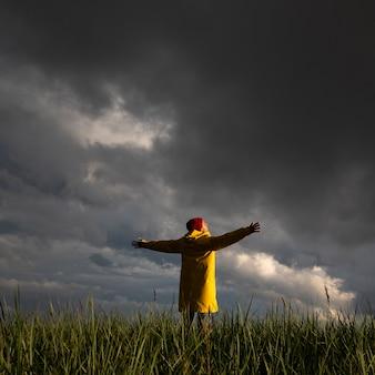 Homem com capa de chuva com as mãos bem abertas em pé no campo