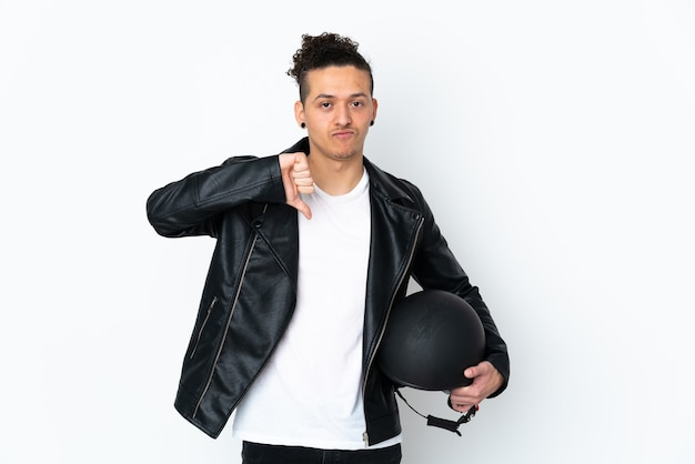 Homem com capacete de motocicleta sobre branco isolado mostrando sinal de polegar para baixo