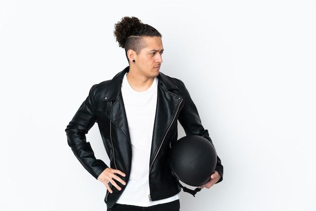 Homem com capacete de motocicleta sobre branco isolado pensando em uma ideia