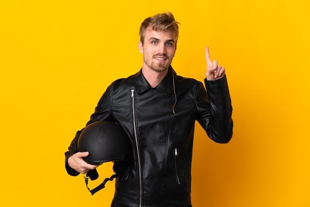 Homem com capacete de motociclista isolado apontando uma ótima ideia