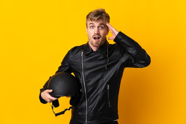 Homem com capacete de motociclista isolado com expressão de surpresa