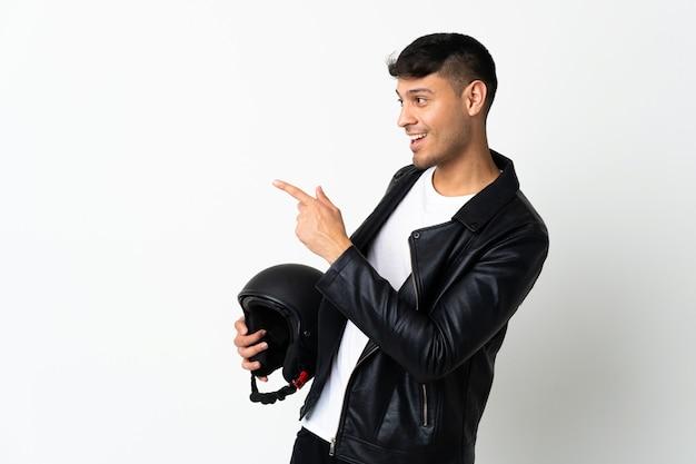 Homem com capacete de motociclista isolado no branco apontando o dedo para o lado e apresentando um produto
