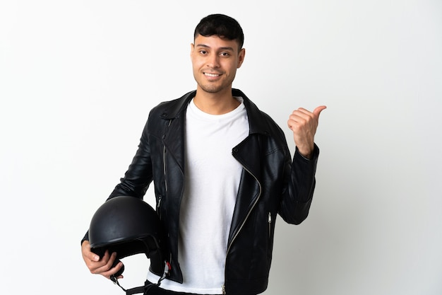 Homem com capacete de motociclista isolado no branco apontando para o lado para apresentar um produto
