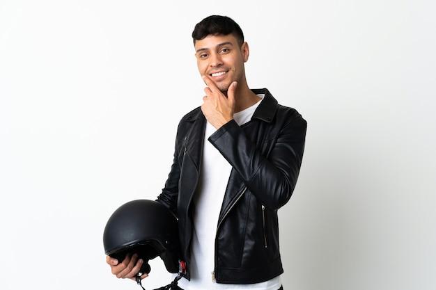 Homem com capacete de motociclista isolado no branco feliz e sorridente