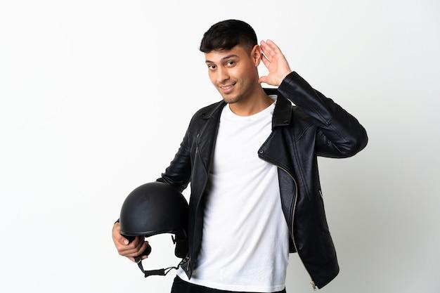 Homem com capacete de motociclista isolado no branco ouvindo algo colocando a mão na orelha
