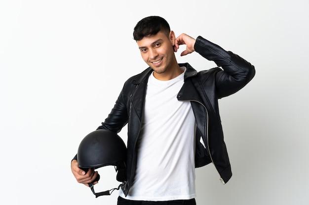 Homem com capacete de motociclista isolado no branco rindo