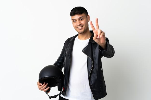 Homem com capacete de motociclista isolado no branco sorrindo e mostrando sinal de vitória