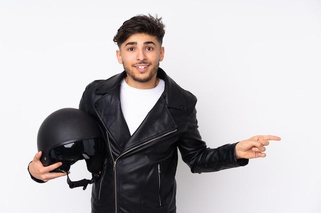 Homem com capacete de motociclista isolado no branco surpreso e apontando o dedo para o lado
