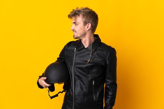 Homem com capacete de motociclista isolado, olhando de lado