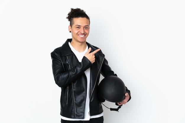Homem com capacete de motociclista sobre branco isolado apontando o dedo para o lado