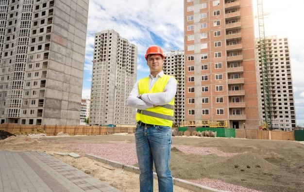 Homem com capacete e colete de segurança em pé no canteiro de obras