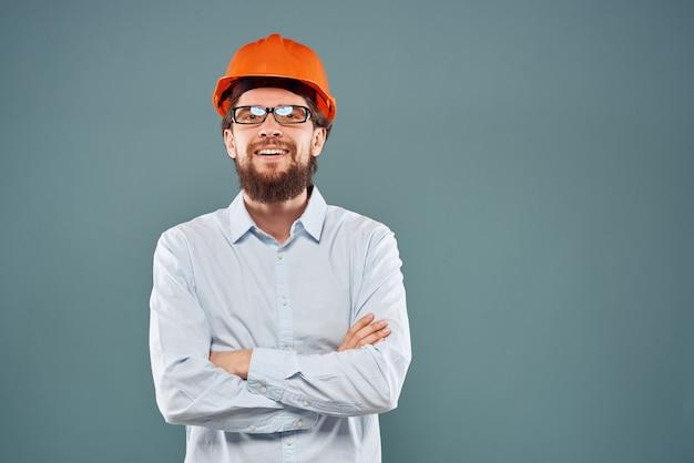 Homem com capacete laranja cortada vista de fundo azul obra de construção