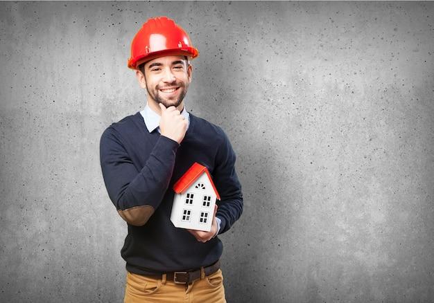 Homem com capacete vermelho e uma pequena casa na mão