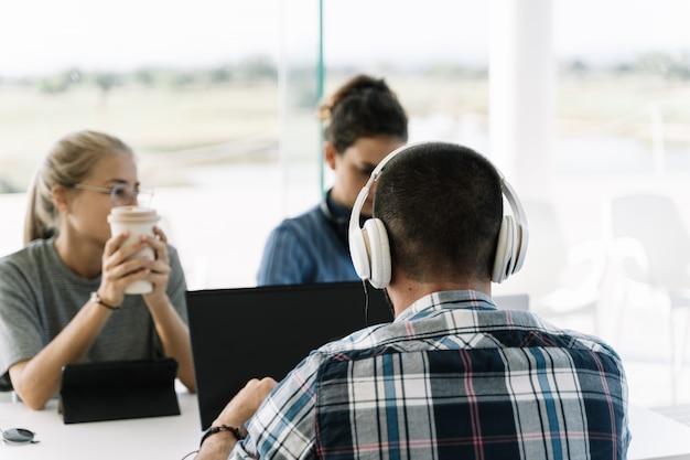 Homem com capacetes brancos, sentado ao lado de duas meninas na mesma reunião de mesa