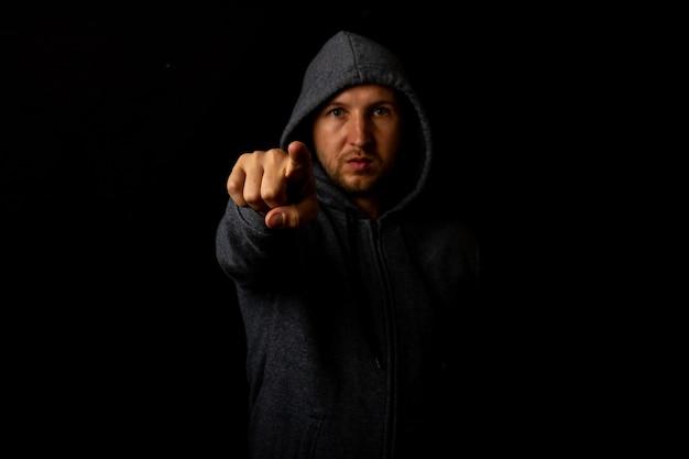 Homem com capuz aponta o dedo contra um fundo escuro.