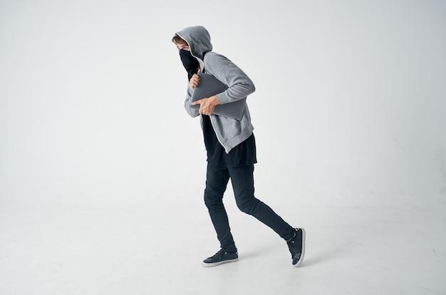 Homem com capuz na cabeça máscara roubo de laptop crime de entrada ilegal