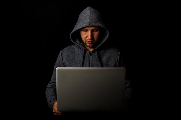 Homem com capuz segura um laptop nas mãos em um escuro