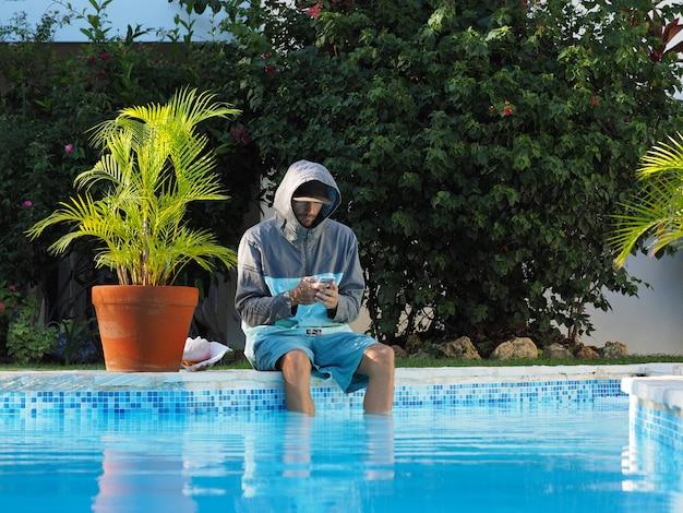 Homem com capuz sentado na piscina, com celular. pernas na água.