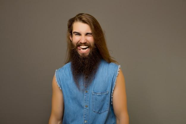 Homem com cara feliz e engraçada, sorrindo e mostrando a língua.