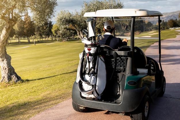 Homem com carrinho de golfe carregando tacos