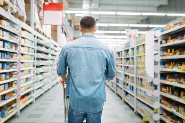 Homem com carrinho faz uma compra no supermercado, vista traseira. cliente masculino na loja, marido com carrinho escolhendo bens de consumo, compras para a família