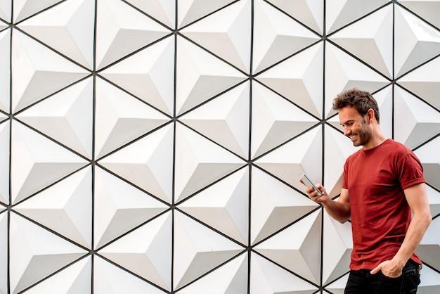 Homem com celular encostado na parede