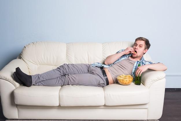 Homem com cerveja e batatas fritas assistindo tv em casa. Foto Premium