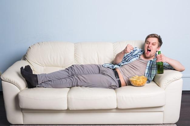 Homem com cerveja e batatas fritas assistindo tv em casa.