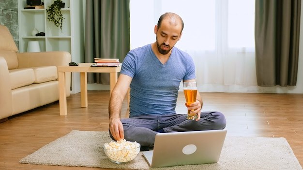 Homem com cerveja e pipoca na videochamada, conversando com amigos durante restrições obscenas.