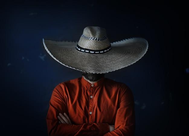 Homem com chapéu de aba de palha escondendo o rosto cara incógnito
