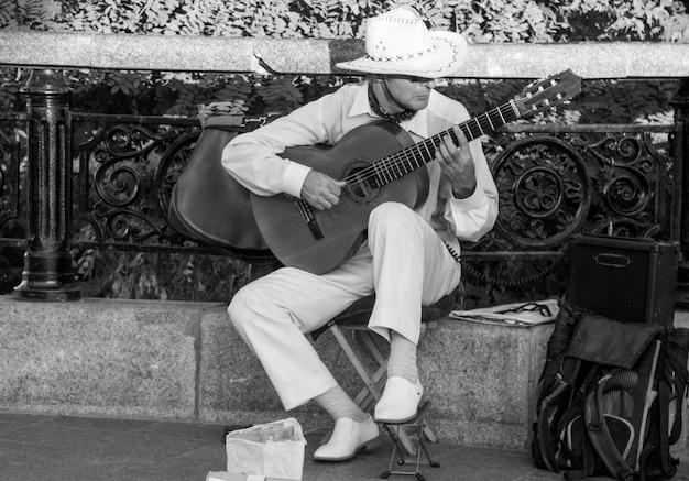 Homem com chapéu de aba larga tocando violão na rua. foto preto e branco