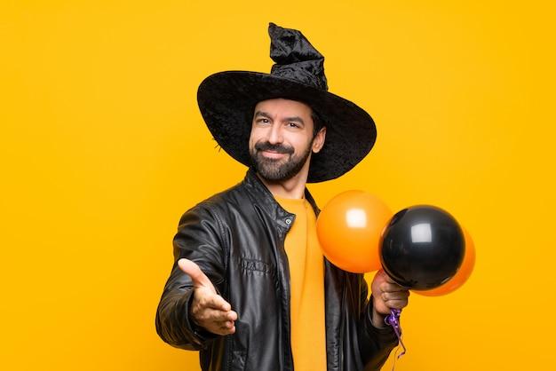 Homem com chapéu de bruxa segurando balões de ar preto e laranja para festa de halloween, apertando as mãos para fechar um bom negócio