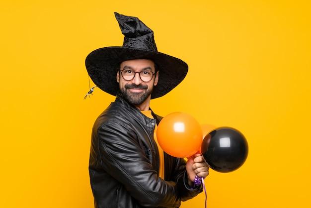 Homem com chapéu de bruxa segurando balões de ar preto e laranja para festa de halloween com óculos e sorrindo