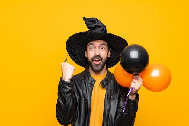 Homem com chapéu de bruxa segurando balões de ar preto e laranja para festa de halloween, comemorando uma vitória na posição de vencedor