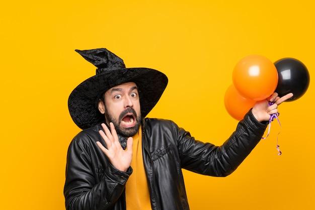 Homem com chapéu de bruxa segurando balões de ar preto e laranja para festa de halloween, nervoso e assustado