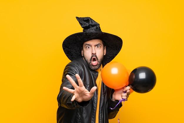 Homem com chapéu de bruxa segurando balões de ar preto e laranja para festa de halloween nervoso, esticando as mãos para a frente
