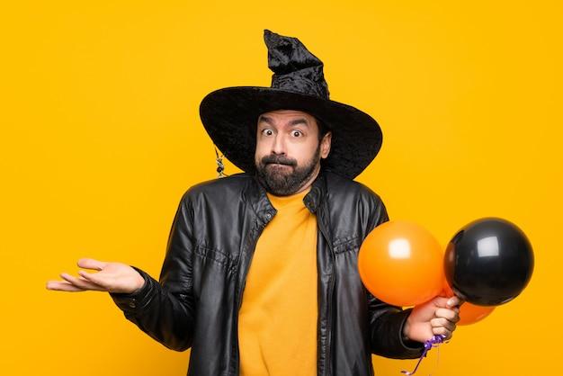 Homem com chapéu de bruxa segurando balões de ar preto e laranja para festa de halloween, tendo dúvidas ao levantar as mãos