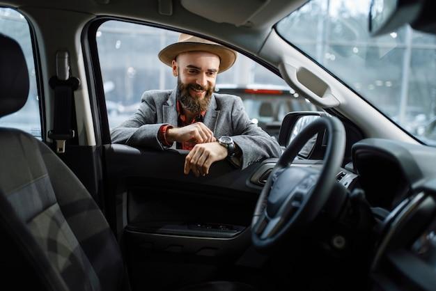 Homem com chapéu de cowboy parece o interior de um automóvel novo na concessionária. cliente no showroom de veículos, homem comprando transporte, concessionária de automóveis