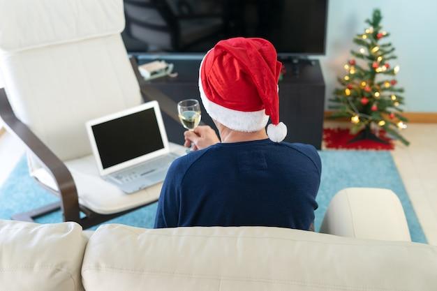 Homem com chapéu de natal brindando na frente do computador. tecnologia de conceito e confinamento.