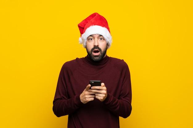 Homem com chapéu de natal com celular sobre fundo amarelo isolado