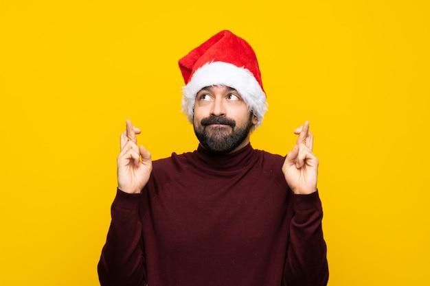Homem com chapéu de natal isolado muro amarelo com dedos cruzando e desejando o melhor